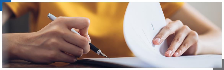 Kobieca dłoń z długopisem przeglądająca dokumenty