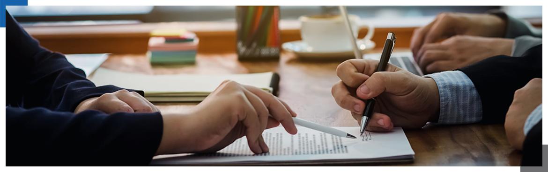Długopisy w dłoniach nad dokumentem